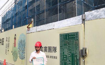 建築師檢查完畢工程告示牌前拍照